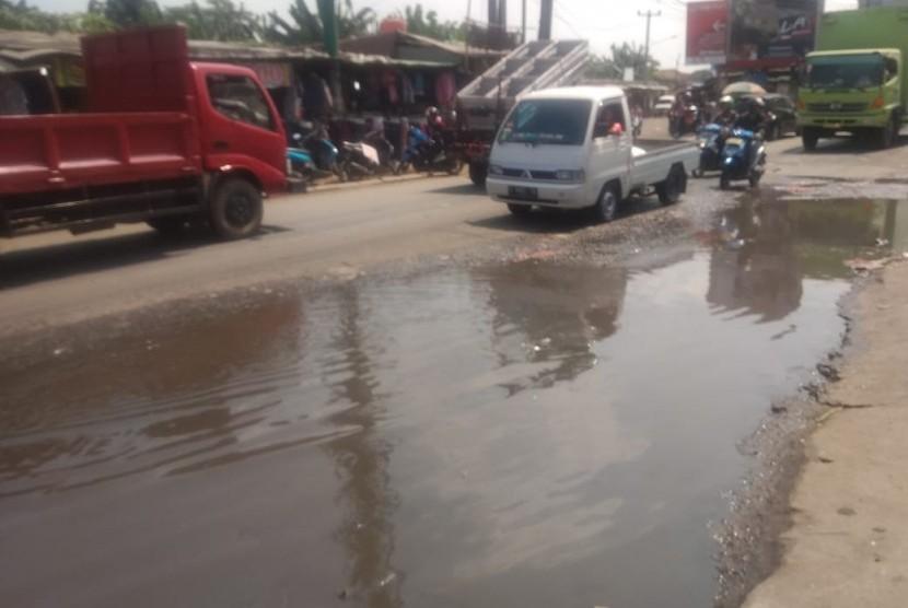 Jalan raya di depan pasar Cileungsi,  Cileungsi,  Kabupaten Bogor kondisnya saat ini rusak dan tergenang oleh air, Senin (20/5).