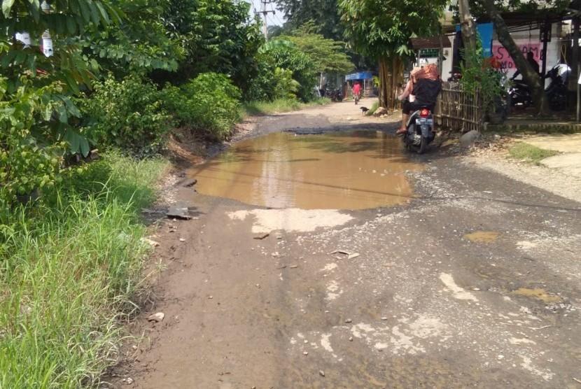 Jalan utama menuju perumahan Telaga Pasir Raya, Serang Baru, Kabupaten Baru kondisinya rusak.