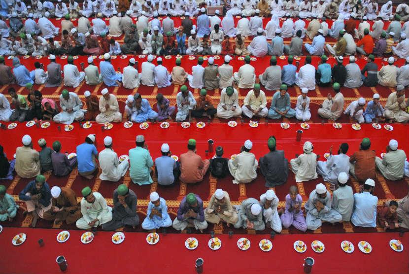 Jamaah menunggu saat berbuka puasa di sebuah masjid di Gujranwala, Pakistan, Ahad (22/7). (Aftab Rizvi/AP)
