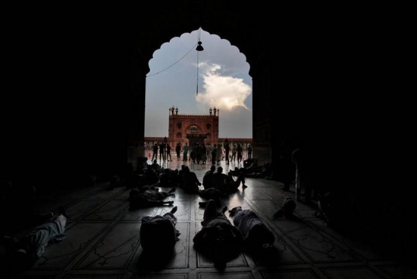 Jamaah Muslim India beristirahat berbaring menunggu waktu berbuka di Masjid Jama, New Delhi, India.