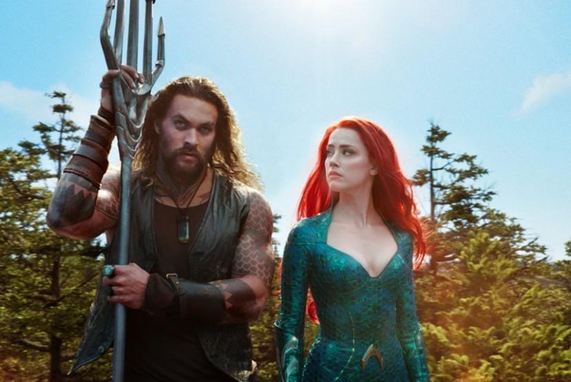 Jason Momoa (kiri) dan Amber Heard dalam adegan film Aquaman.