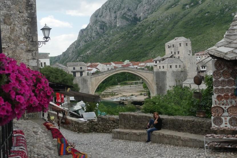Jembatan Mostar beserta pemandangan pegunungan dan bunga berwarna merah.