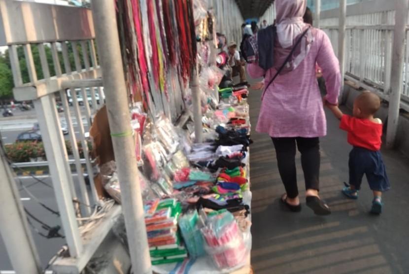 Jembatan Penyeberangan Orang (JPO) Halte Transjakarta S Parman,  Podomoro City, Jakarta Barat dipenuhi oleh sejumlah Pedagang Kaki Lima, Jumat (17/5).