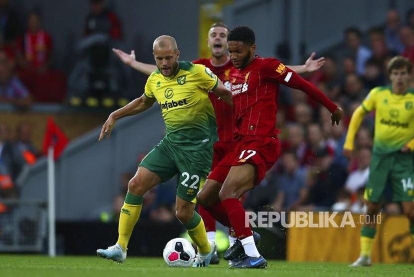 Joe Gomez (kanan) dan Teemu Pukki (kiri) berebut bola pada laga liga Inggris antara Liverpool  melawan Norwich City  di Anfield Stadium, Liverpool, Ahad (11/8) waktu setempat.