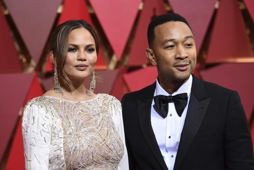 John Legend (kanan) dan istrinya Chrissy Teigen di karpet merah Piala Oscar, (27/2).