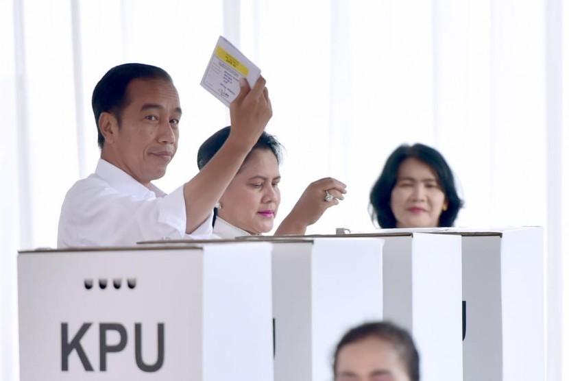 Jokowi menunjukkan kertas suara.