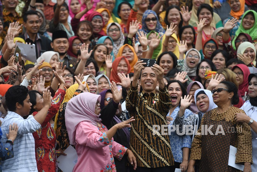 Jokowi Temui Komunitas Perempuan. Presiden Joko Widodo (tengah) berswafoto dengan komunitas perempuan akar rumput usai pertemuan di Istana Merdeka, Jakarta, Rabu (6/3/2019).