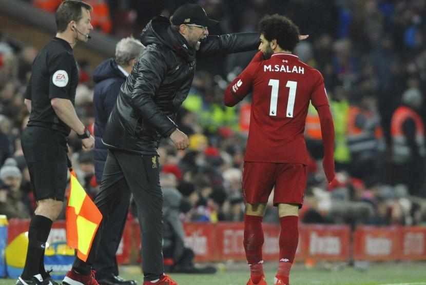 Juergen Klopp (tengah) memberikan instruksi kepada Mohamed Salah.