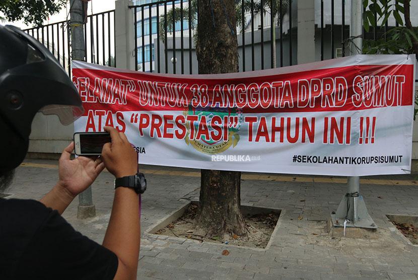 Jurnalis memotret spanduk menyikapi penetapan tersangka 38 anggota DPRD Sumut periode 2009-2014 dan 2014-2019 yang dipasang di kawasan gedung dewan di Medan, Sumatra Utara, Jumat (13/4).