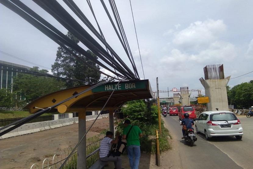 Kabel listrik di jalan raya Bekasi Jakarta, Cakung, Jakarta Timur menjuntai hingga ke trotoar jalan.