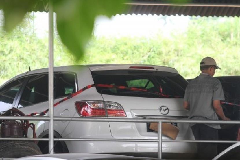 Kader PKS melintas usai menutupi plat nomor mobil Mazda CX9 B 2 MDF berwarna putih yang diduga milik Lutfhi Hasan Ishaaq disita KPK diparkir di halaman DPP PKS, Jakarta, Selasa (7/5).