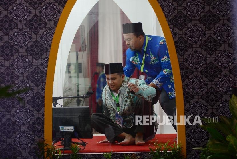 Kafilah Tuna Netra dibantu oleh panitia untuk keluar mimbar usai membacakan ayat suci Al Quran saat menjalani sesi final lomba Tilawah Al Quran dalam rangkaian MTQ Nasional ke XXVI yang diadakan di Aula Rinjani Gedung BKD, Kota Mataram, Nusa Tenggara Barat