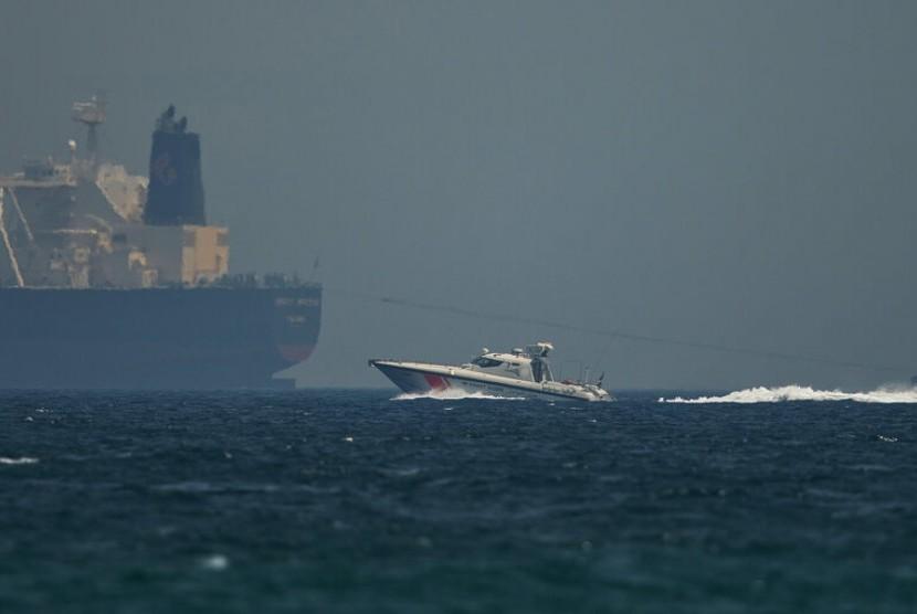 Kapal penjaga pantai Uni Emirat Arab (UEA) melewati kapal tanker minyak di perairan Fujairah, UEA, Senin (13/5).