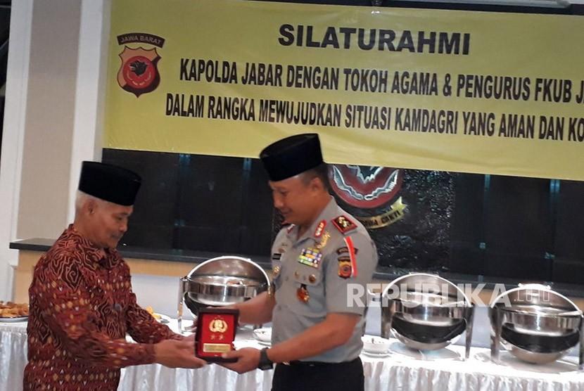 Kapolda Jabar, Irjen Pol Drs Agung Budi Maryoto menyerahkan cinderamata kepada Ketua FKUB Jabar, H Rafani Achyar.