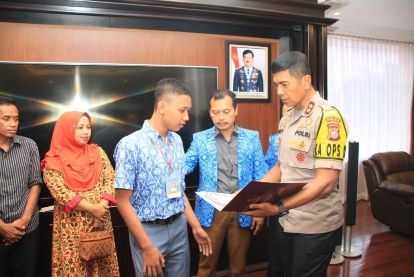 Kapolda Jabar Irjen Pol Rudy Supahridi memberikan penghargaan kepada Mochammad Ridwan Suryana, siswa kelas XII SMK Pasundan, Kabupaten Cianjur karena membantu Aiptu Erwin.