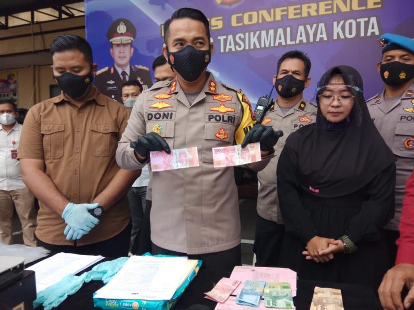 Kapolres Tasikmalaya Kota AKBP Doni Hermawan memperlihatkan uang palsu saat konferensi pers pengungkapan kasus peredaran uang palsu, Rabu (28/4).