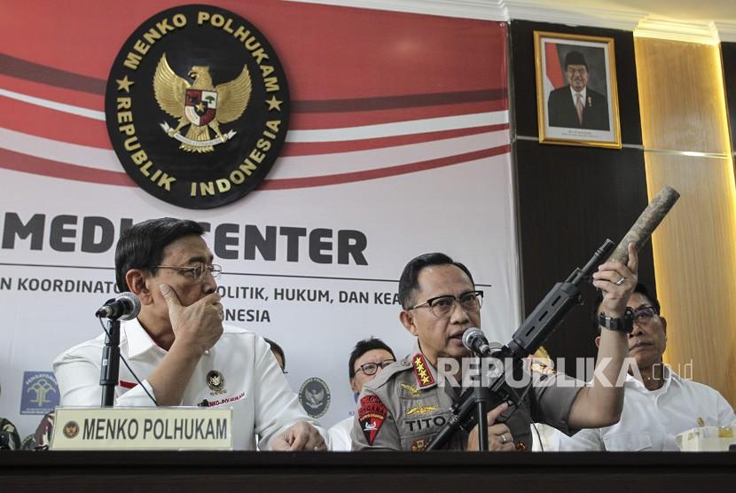 Kapolri Jenderal Pol Tito Karnavian (tengah) disaksikan Menko Polhukam Wiranto (kiri) dan Kepala KSP Moeldoko (kanan) menunjukkan barang bukti senjata api saat menyampaikan konferensi pers perkembangan pascakerusuhan di Jakarta dini hari tadi, di kantor Kemenko Polhukam, Jakarta, Rabu (22/5/2019).