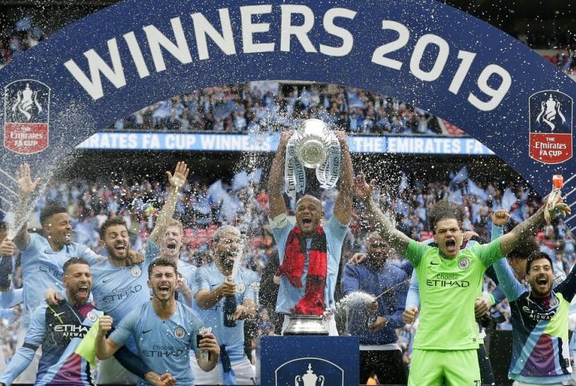 Kapten Manchester City, Vincent Kompany mengangkat trofi Piala FA.