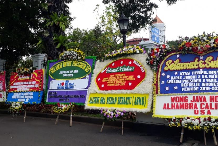 Karangan bunga ucapan selamat kepada paslon Jokowi-Ma'ruf tampak berjejer di halaman pintu masuk Istana Presiden, Jakarta, Senin (22/4).