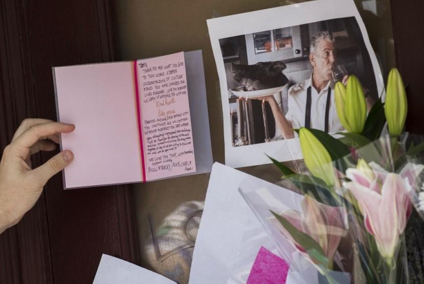 Kartu simpati ditinggalkan dengan foto Anthony Bourdain di luar bangunan yang dulunya merupakan restoran Le Halles di Park Avenue, New York, Sabtu (9/6).