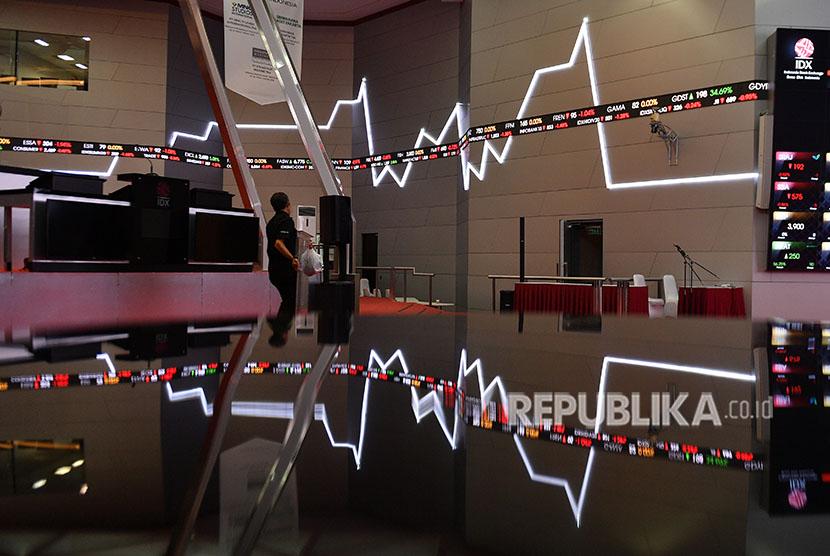 Karyawan melintas di dekat monitor pergerakan Indeks Harga Saham Gabungan (IHSG) di Bursa Efek Indonesia, Jakarta. ilustrasi