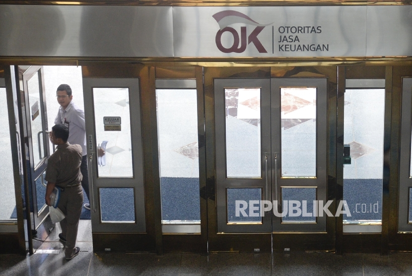 Karyawan melintas di pintu masuk Otoritas Jasa Keuangan (OJK) di Jakarta, Senin (23/10).