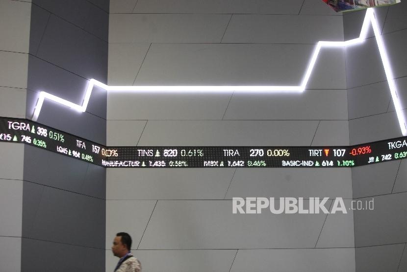 Karyawan melintasi layar Indeks harga saham gabungan (IHSG) di Bursa Efek Indonesia (BEI) Jakarta, Senin (7/8).
