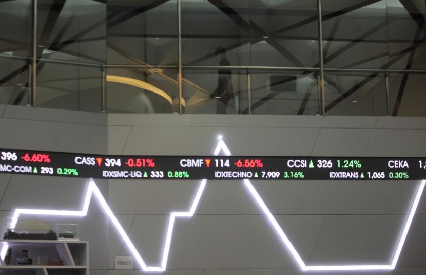Karyawan melintasi layar monitor pergerakan Indeks Harga Saham Gabungan (IHSG) di Bursa Efek Indonesia, Jakarta, Jumat (11/6/2021). PT BNP Paribas Asset Management hari ini meluncurkan Reksa Dana Indeks BNP Paribas IDX Growth30 ETF.