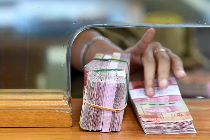 Karyawan memegang mata uang rupiah di gerai penukaran mata uang asing. ilustrasi