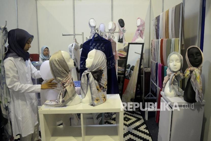 Karyawan menata produk fasion muslim yang di pamerakan pada The 2nd Indonesia Internasional Halal Lifestyle Expo & Conference (INHALEC) di Balai Kartini, Jakarta, Kamis (19/10).