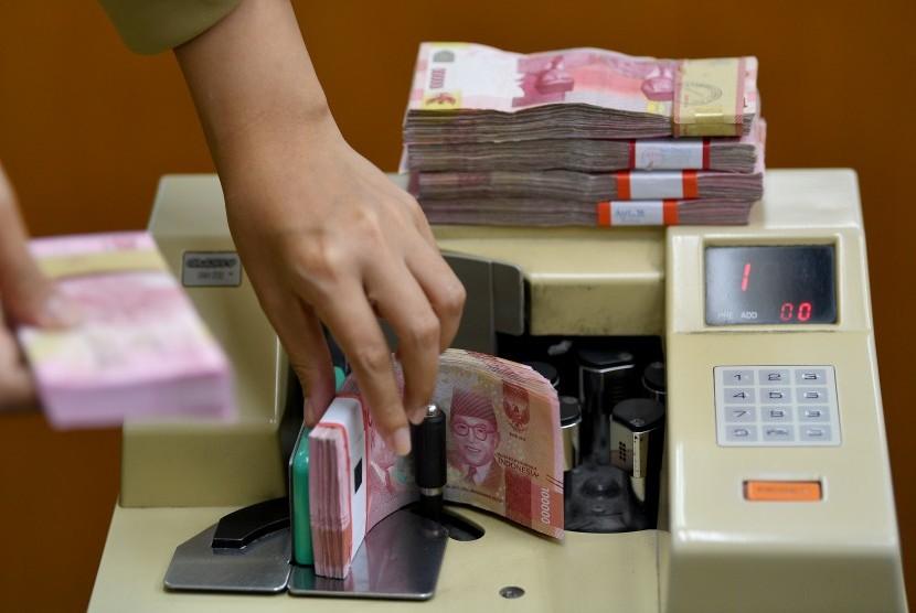 Karyawan menghitung mata uang rupiah di gerai penukaran mata uang asing Ayu Masagung, Kwitang, Jakarta Pusat, Senin (28/1/2019).