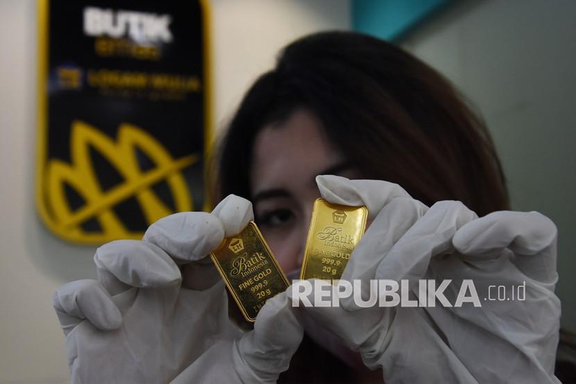 Karyawan menunjukan emas batangan yang dijual di Butik Emas Antam. ilustrasi
