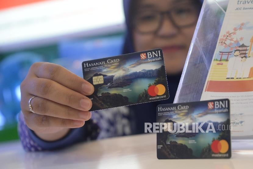 Karyawan menunjukkan Kartu BNI IB Hasanah Card spesial desain Lombok saat peluncuran, Jakarta, Jumat (22/9).