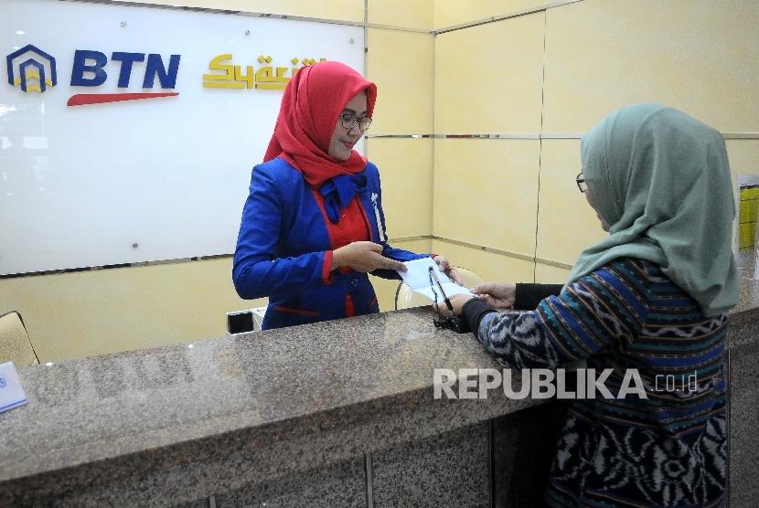 Karyawati melayani nasabah di Banking Hall Bank BTN Syariah, Jakarta, Selasa (30/5). PT Bank Tabungan Negara (BTN) bekerjasama dengan PT Sarana Multigriya Finansial terkait transaksi sekuritas pembiayaan pemilikan rumah (KPR iB) dengan skema Efek Beragun Aset Syariah berbentuk Surat Partisipasi (EBAS-SP).