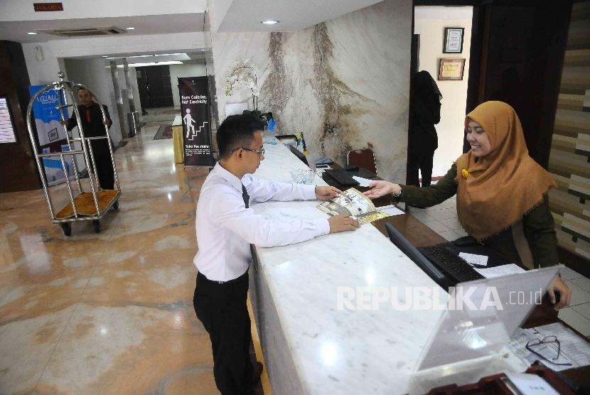 Karyawati melayani tamu yang hendak menginap di hotel (ilustrasi).
