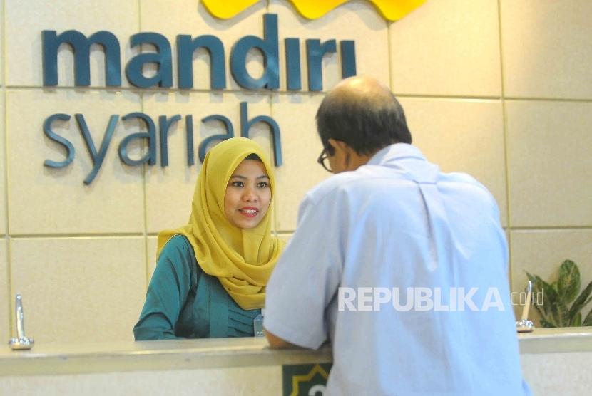 Karyawati mengenakan kebaya melayani nasabahnya di Banking Hall Bank Syariah Mandiri, Jakarta, Kamis (21/4).  (Republika/ Agung Supriyanto )