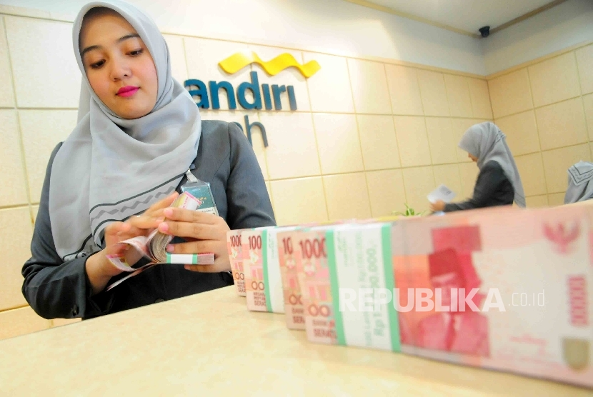 A teller was counting money at Banking Hall Bank Syariah Mandiri, Jakarta. The assets of sharia banks rose 18.49 percent y-o-y to Rp305.5 trillion by July, 2016 on growing third party funds.