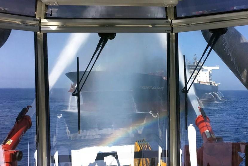 Kebakaran di kapal tanker Front Altair terlihat dari jendela observasi sedang berusaha dipadamkan dengan water cannon di Teluk Oman, Kamis (13/6).