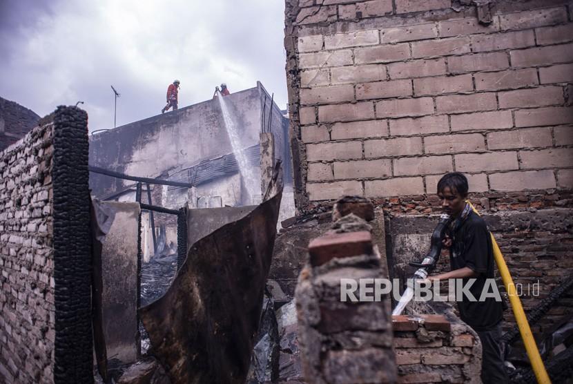Kebakaran di Krukut Taman Sari. Petugas pemadam kebakaran bersama warga melakukan pendinginan pascakebakaran yang melanda permukiman padat penduduk di Jalan Ketapang Utara, Krukut, Tamansari, Jakarta, Selasa (26/2/2019).