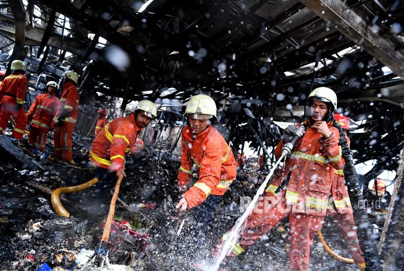 Kebakaran Pasar Blok A. Petugas pemadam kebakaran mendinginkan sisa kebakaran di Tempat Penampungan Sementara Pasar Blok A, Kebayoran Baru, Jakarta Selatan, Rabu (6/3).