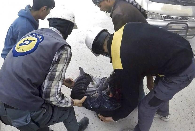Kelompok Syrian Civil Defense menolong seorang warga yang terluka setelah serangan udara terjadi di Ghouta, Damaskus, Suriah, Kamis (1/3).