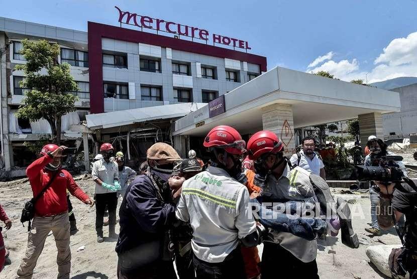 Keluarga korban dibawa petugas usai menyaksikan jenazah keluarganya yang menjadi korban gempa tsunami Palu di Hotel Mercure, Palu, Sulawesi Tengah, Jumat (5/10).