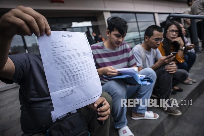 Keluarga korban kecelakaan penerbangan Lion Air PK - LQP nomor penerbangan JT 610 menunjukkan surat keterangan dari Lion Air kepada wartawan di halaman Hotel Ibis, Cawang, Jakarta, Rabu (23/1/2019).