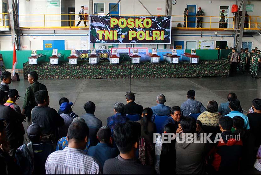 Keluarga korban mengikuti serah terima jenazah korban penembakan kelompok kriminal bersenjata (KKB) di hanggar Avco Bandara Moses Kilangin Timika, Mimika, Papua, Jumat (7/12)