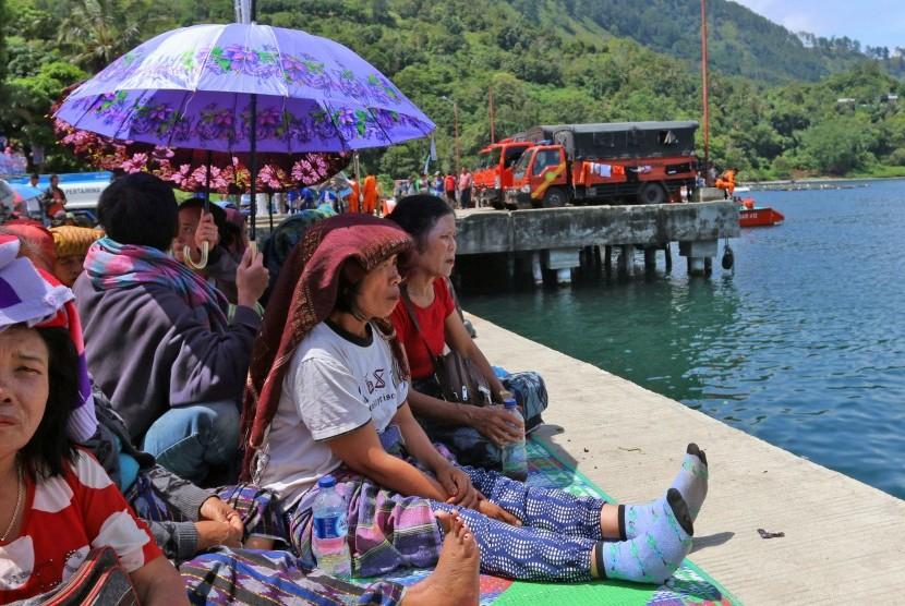 Keluarga korban tenggelamnnya KM Sinar Bangun menunggu di dermaga Pelabuhan Tigaras, Danau Toba, Simalungun, Sumatera Utara, Jumat (22/6).