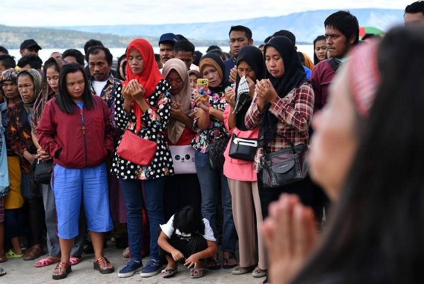 Keluarga korban tenggelamnya KM Sinar Bangun bersama warga mengikuti doa lintas agama di dermaga Tigaras, Danau Toba, Simalungun, Sumatera Utara, Minggu (1/7).