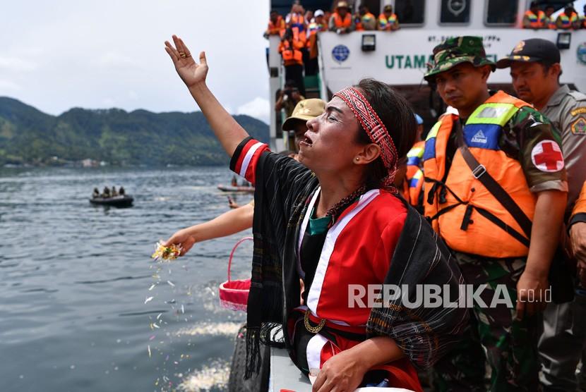 Keluarga korban tenggelamnya KM Sinar Bangun memanjatkan doa dalam prosesi tabur bunga di kawasan titik tenggelamnya kapal di Danau Toba, Sumatera Utara, Senin (2/7).