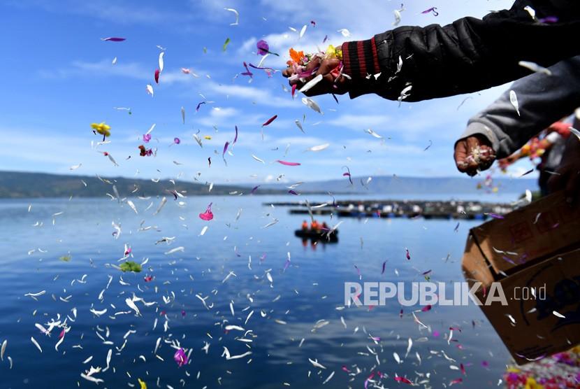 Keluarga korban tenggelamnya KM Sinar Bangun menabur bunga di Dermaga Tigaras, Danau Toba, Simalungun, Sumatera Utara, Selasa (3/7).