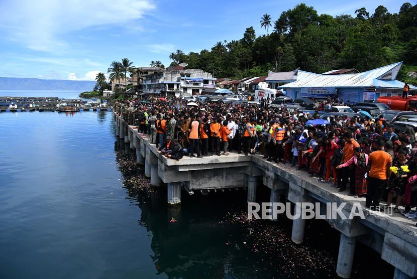 Keluarga korban tenggelamnya KM Sinar Bangun menabur tabur bunga di Dermaga Tigaras, Danau Toba, Simalungun, Sumatera Utara, Selasa (3/7).