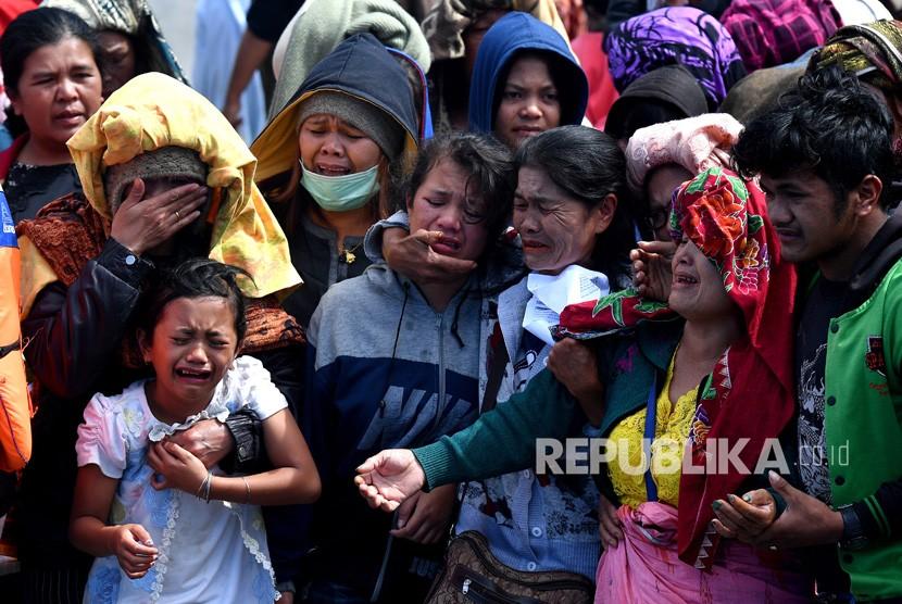 Keluarga korban tenggelamnya KM Sinar Bangun menangis saat tabur bunga di Dermaga Tigaras, Danau Toba, Simalungun, Sumatera Utara, Selasa (3/7).
